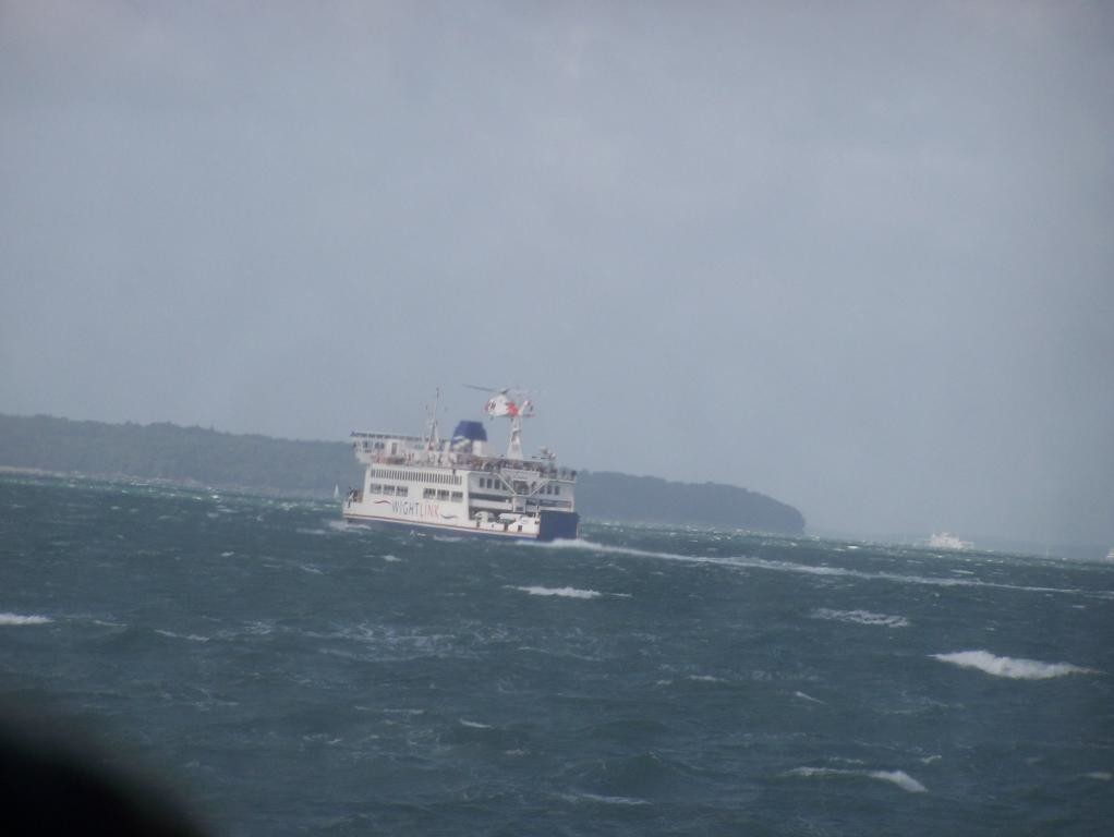 helicopter hovering over car ferry on way to isle of wight